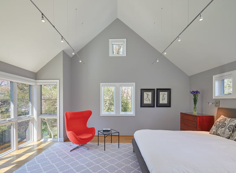 The new master bedroom, on the second floor of the addition, overlooks the spacious front yard through tall windows.