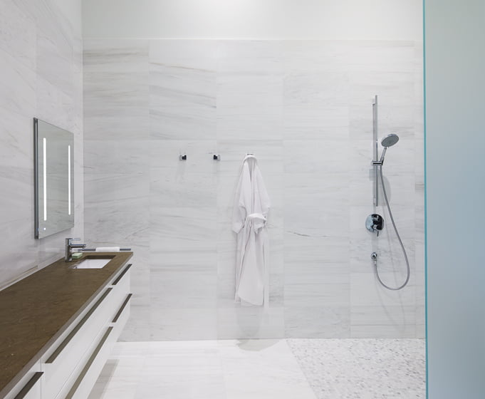The master bathroom has floor tiles and a shower lined in marble from Stone Source.