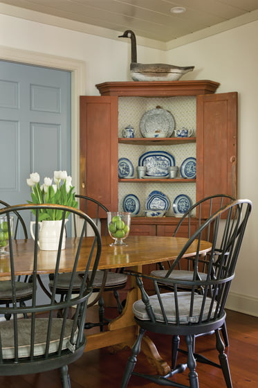 The same soft, custom blue visually connects the casual, rustic breakfast area to the home's front door.
