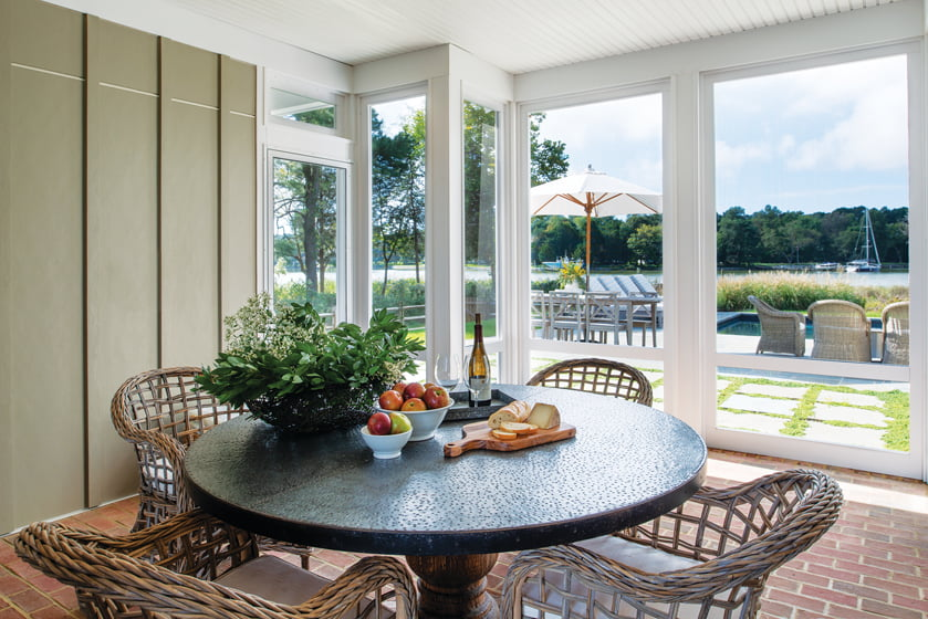 A screened porch holds a hammered zinc-topped table on a raw-wood base.
