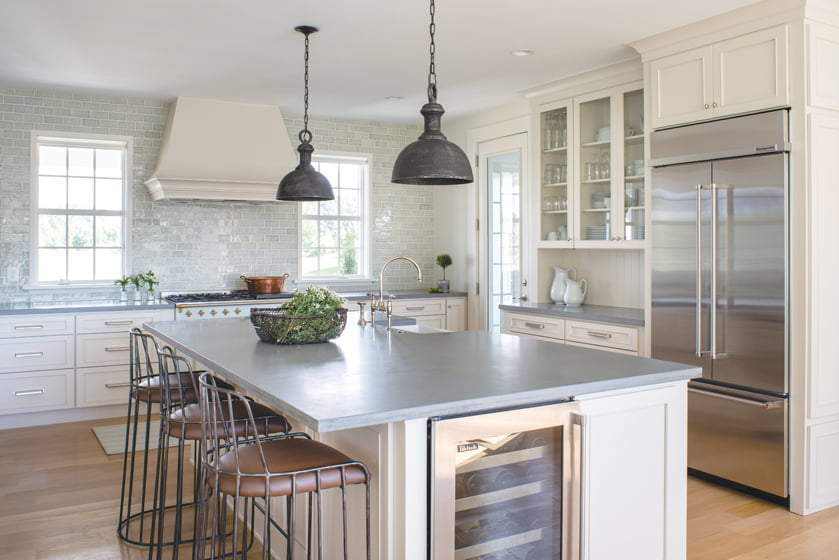 In the kitchen, Noir Furniture stools pull up to the island; wrought-iron Currey & Company pendants hang above it.