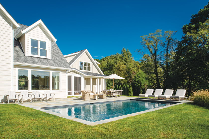The pool area boasts furnishings in pre-weathered wicker and gray-washed teak.