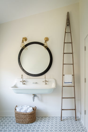 The powder room features an encaustic cement-tile floor, vintage sink and antique ladder doubling as a towel holder.