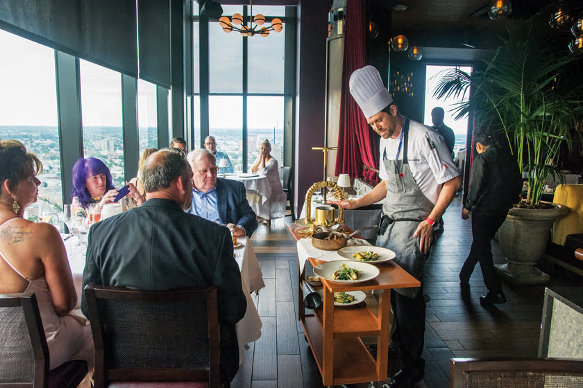 The Bygone's executive chef Matthew Oetting plates a dish on a gueridon trolley tableside. © Atlas Restaurant Group.