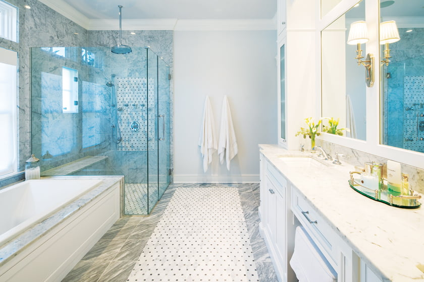 The marble-clad master bath boasts a universally designed shower enclosure with a curb-less entry and extra-wide doors.