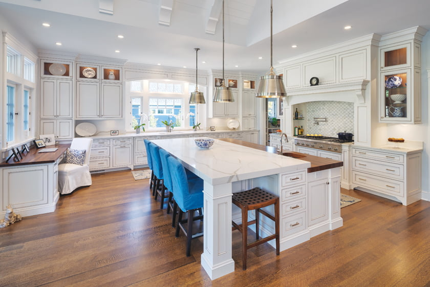 A massive island is perfect for both seating and serving; accents on the traditional white cabinetry keep it from looking sterile.