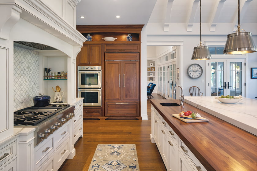 A wall of walnut cabinetry houses the double ovens and paneled fridge.