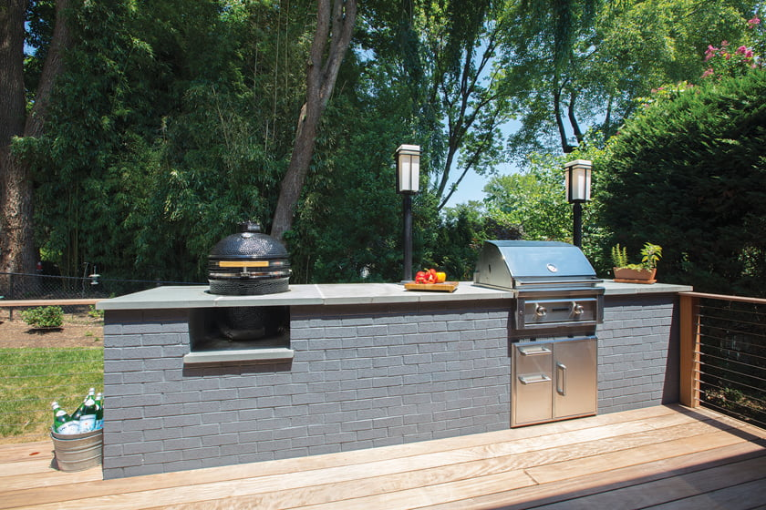 An outdoor kitchen features a Coyote smoker and a Lynx grill.