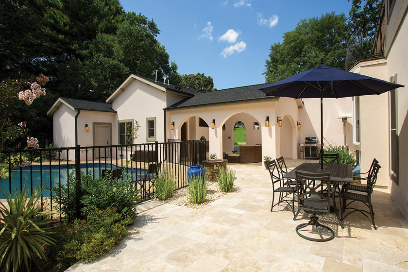 An addition to a Great Falls home is linked to the house by a stucco privacy wall.