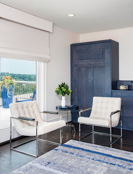 Murphy beds are concealed in blue cabinetry by Hardwood Artisans behind tufted Thayer Coggin chairs.