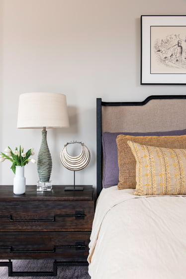 A Currey & Company lamp graces the nightstand; the bed is by Brownstone.