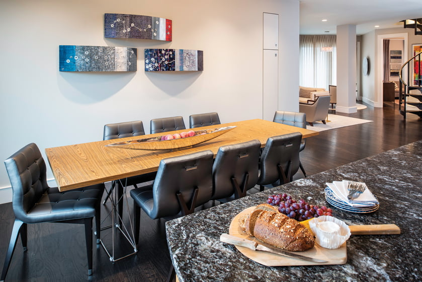 Sculptures by Francie Hester hang above a Modloft table and chairs from Artistic Frame in the kitchen/dining area.