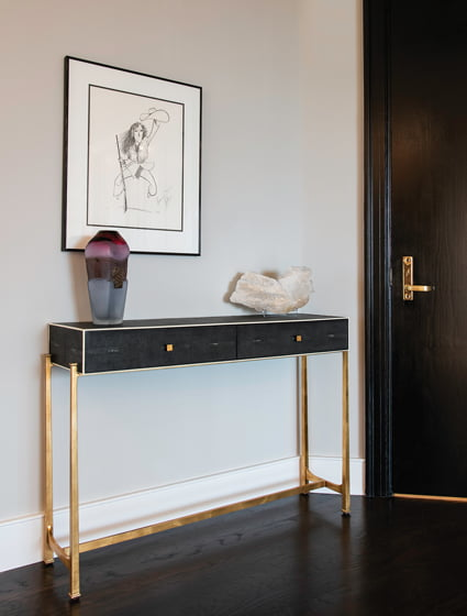 A black-painted door and a black console with brass accents set a glamorous tone at the entry.