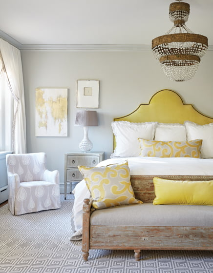 The master bedroom combines a Swedish bench and Continental chandelier with a headboard in Holly Hunt velvet.