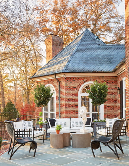 The bluestone-and-brick rear terrace offers room to relax around Mr. Brown cocktail tables.