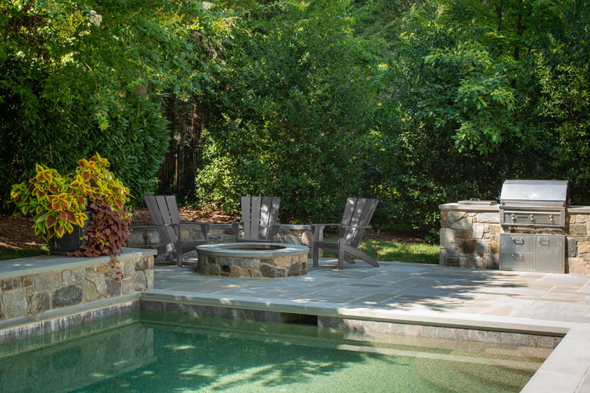 Anthony Wilder Design/Build's landscape design for a Gibson Island family features a fire pit beside the pool.