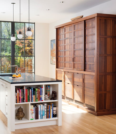 A custom walnut cabinet holds a beverage bar, freezer and pantry. © Stacy Zarin Goldberg