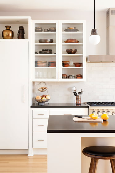 Glass-fronted Greenfield cabinetry displays decorative dishware. © Stacy Zarin Goldberg