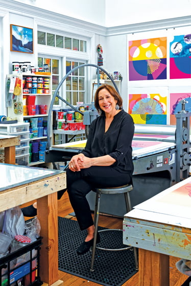 Susan Goldman sits by the printing press in her Rockville studio. Portrait by Bob Narod.