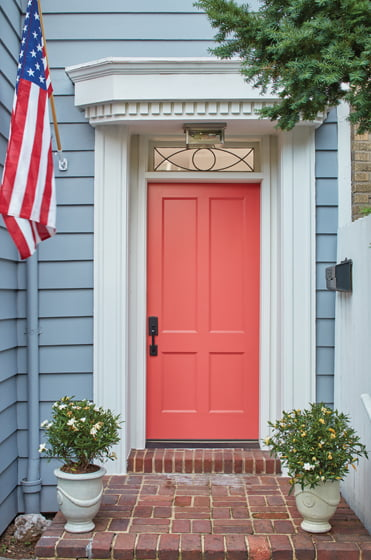 Renovated by StudioMB, a traditional Georgetown row house features a front door painted in  a bold coral hue.