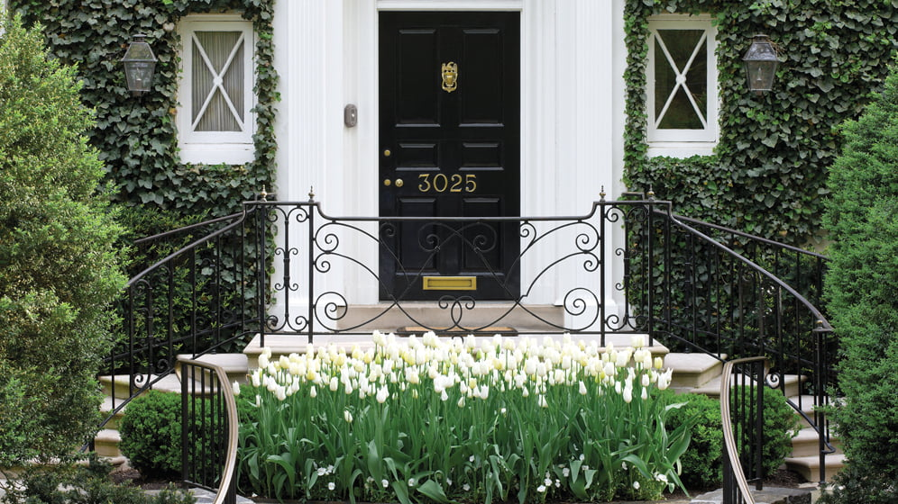 The home's formal entranceway is enhanced by ivy cultivated to soften the masonry façade.