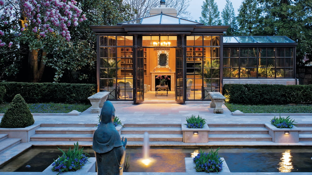 The conservatory spills out onto the French limestone pool terrace; Outdoor Illumination installed the exterior lighting.