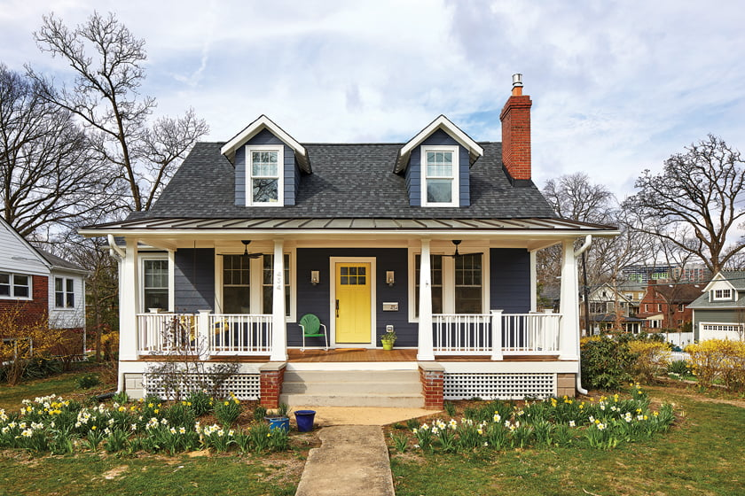 The house is clad in deep-blue HardiePlank, accented by a front door painted in Benjamin Moore's Early Dawn.