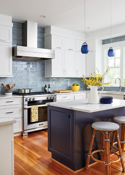 The new kitchen centers on an island painted in Benjamin Moore's Hale Navy with a glass-tile backsplash.
