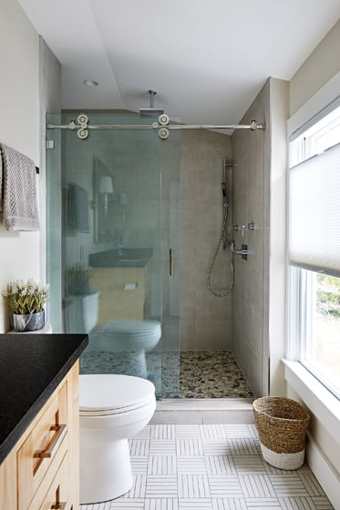 The master bath now accommodates a larger shower enclosure, with porcelain and ceramic tile conveying a modern look.