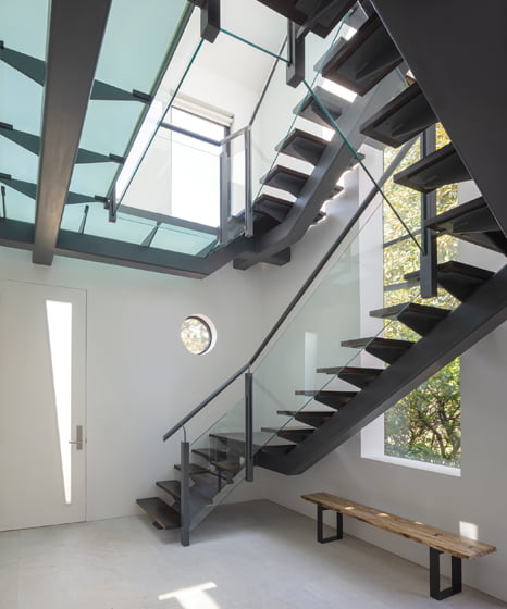 The sculptural glass-and-steel staircase from Jameson's first redo retains its timeless, modern appeal.