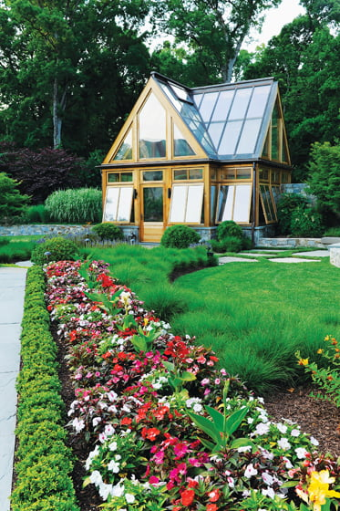 A lush landscape by Surrounds features a greenhouse by Tanglewood Conservatories. © Bob Narod