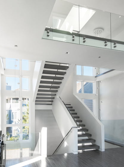 Mark McInturff likens the steel bolts fastening glass railings over the stairwell—as well as the suspended Bocci light fixtures—to jewelry.