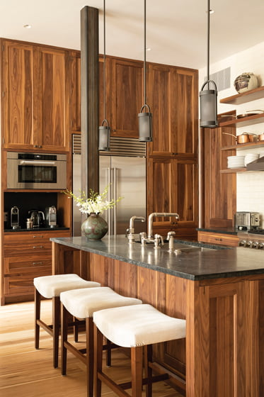 In the kitchen, walnut cabinetry fabricated by Gaston & Wyatt is paired with soapstone countertops.