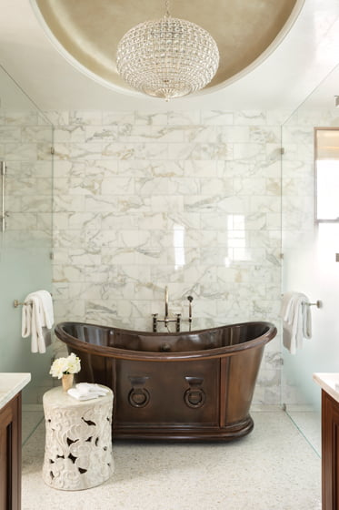 The antique copper tub in the master bath inspired an oval tray ceiling adorned with a silver-leaf finish by Lenore Winters Studio.