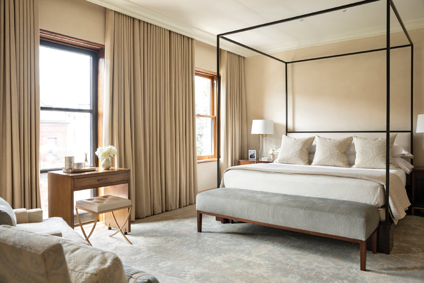 The third-floor master bedroom introduces a touch of pale blue to the neutral palette.