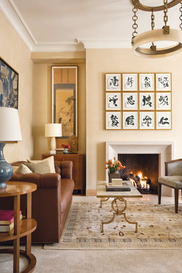 In the study, a set of 19th-century Japanese calligraphic paintings conceals a TV above the limestone fireplace.