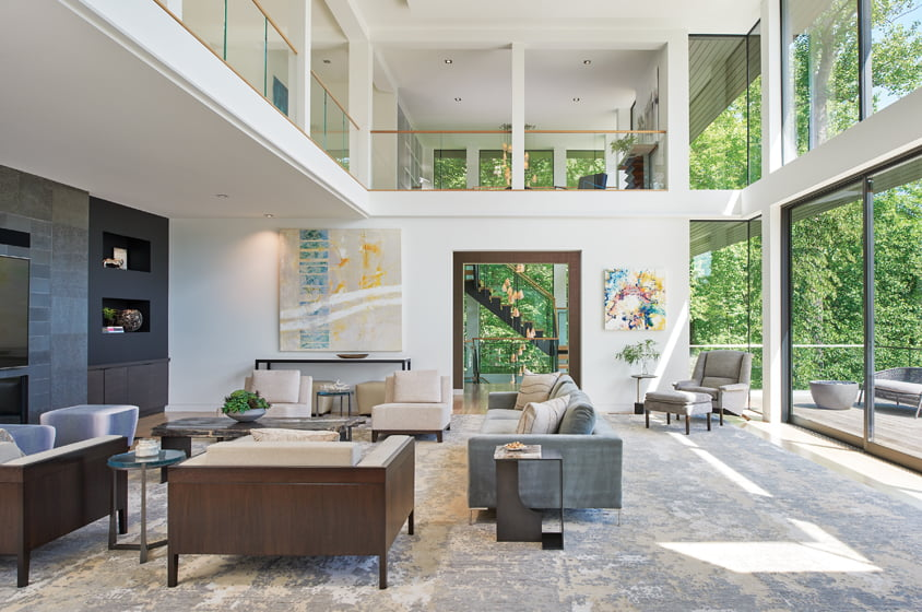 Expanses of smooth and flamed basalt frame the TV and fireplace in the River Room; an Anne Marchand painting hangs above a custom console. A glass-railed balcony on the second floor extends to the owners' private quarters. Stacked-glass doors slide open to create easy flow out to the large ipe deck.