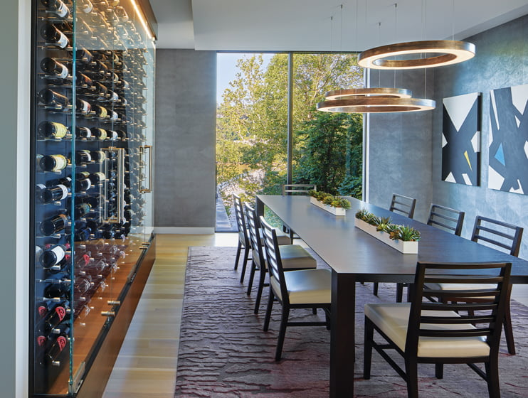 Phillip Jeffries molded-paper wall covering and a custom-built wine-storage display envelop the dining room.