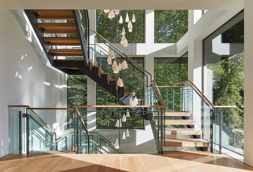 A Bocci fixture is suspended above the floating staircase combining white-oak risers, glass rails and steel supports.