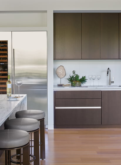 Dark-stained touch-latch wood cabinetry defines an open bar area next to the waterfall-edged island.