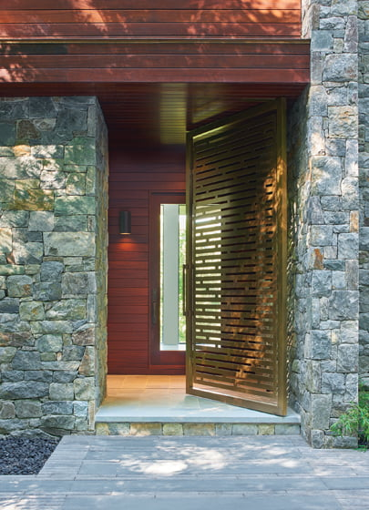 A six-by-10-foot, slatted bronze door serves as a first point of entry