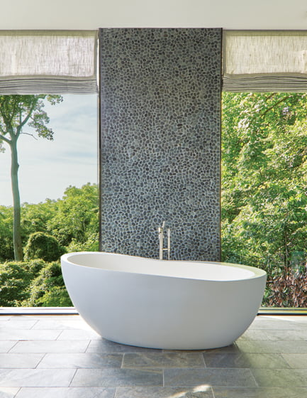 In the master bathroom, slate floors and a river rock feature  wall by Mosaic Tile are organic foils to a sculptural Waterworks tub.