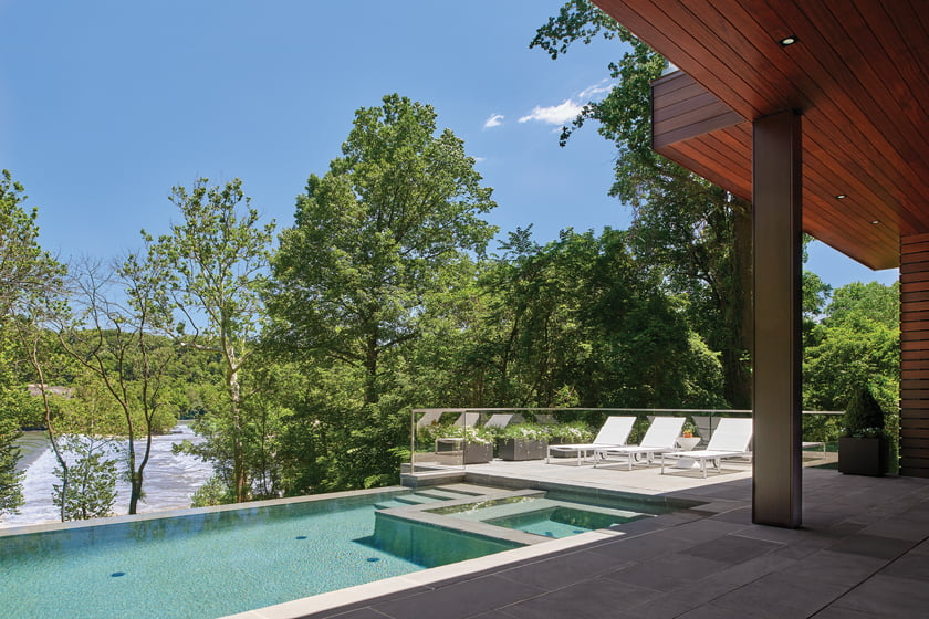 An infinity pool and surrounding bluestone patio are located on the home's lower level, outside the rec room.