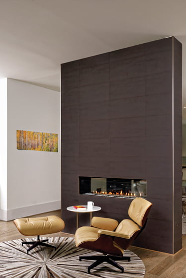 A double-sided fireplace clad in porcelain tile separates the living and dining areas. © Bob Narod