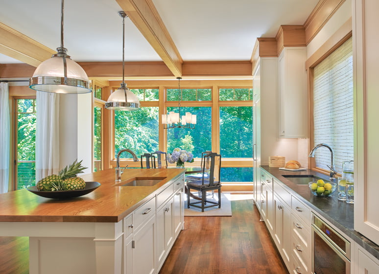 Countertops of reclaimed wood on the island and soapstone at the window provide practical surfaces in the kitchen.