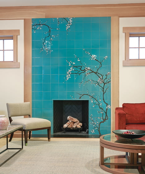 An Asian-inspired ceramic cherry blossom mural from Fire Clay Tile surrounds the living room fireplace.