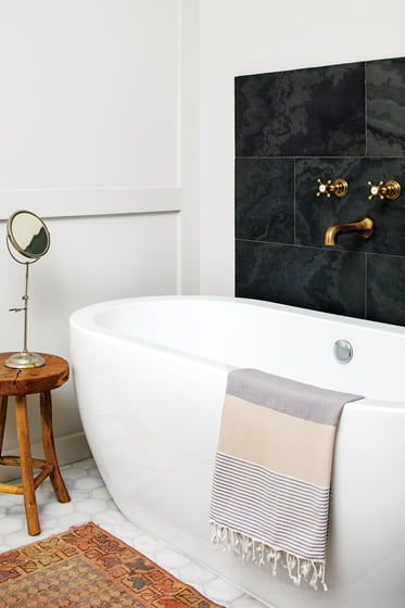 A new soaking tub is anchored by a panel of honed black marble.
