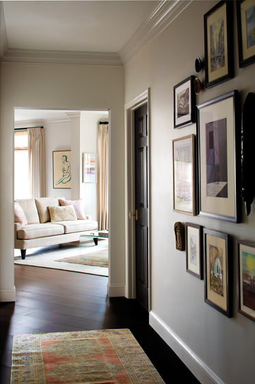 A gallery wall displaying art and objects leads from the entry into the main living space.