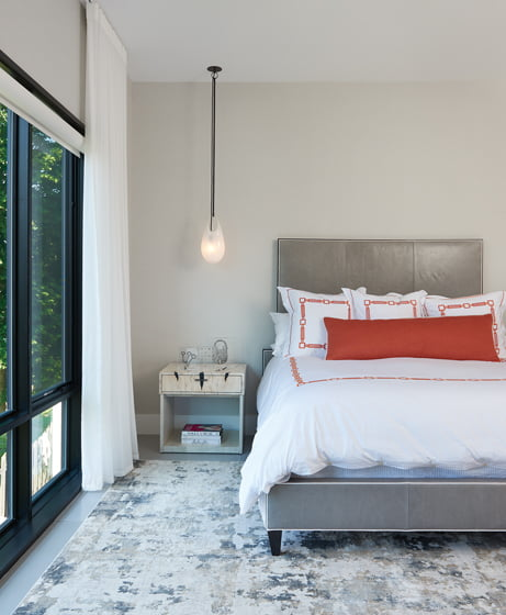 The master bedroom is outfitted in white, gray and pops of orange. © Anice Hoachlander