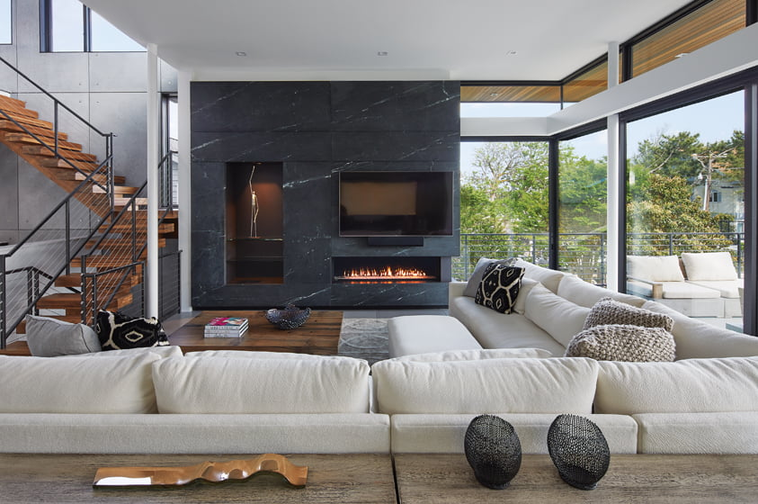 The living area boasts expanses of glass and a soapstone fireplace. © Anice Hoachlander